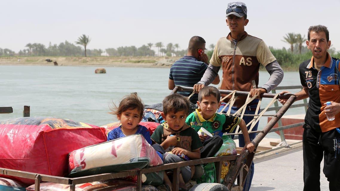 Children sit in a trolley as displaced people from Ramadi cross Bzabz bridge 65 km west of Baghdad, Iraq, Saturday, April 18, 2015. (AP)