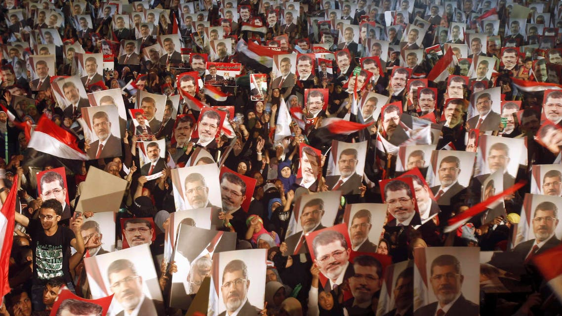Members of the Muslim Brotherhood and supporters of Egypt's President Mohamed Mursi hold pictures of him as they react after the Egyptian army's statement was read out on state TV, at the Raba El-Adwyia mosque square in Cairo in this July 3, 2013 file photo. (Reuters)