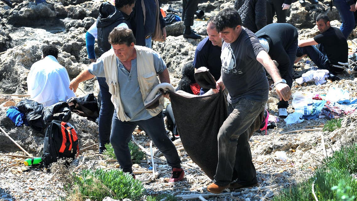 Men carry a dead body inside a blanket on the shore in the eastern Aegean island of Rhodes,Greece on Monday, April 20, 2015 .Greek authorities said that at least three people have died, including a child, after a wooden boat carrying tens migrants from ran aground off the island of Rhodes. (AP Photo//Nikolas Nanev)