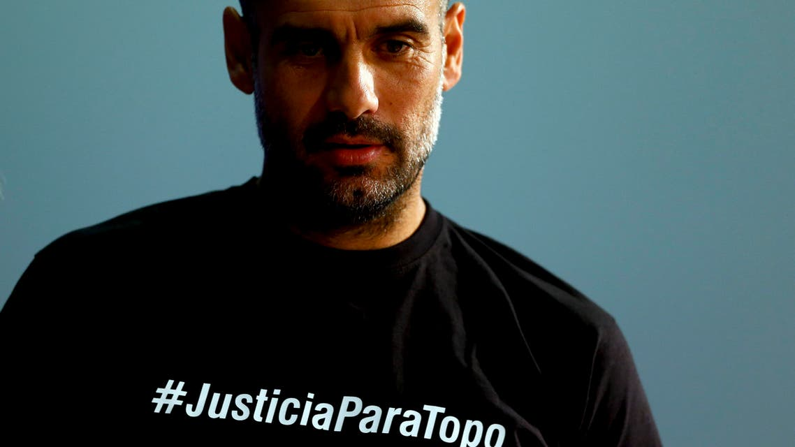 Bayern's head coach Pep Guardiola from Spain wears shirt remembering killed sport journalist Julio 'Topo' Lopez as he arrives for a news conference prior to the Champions League quarterfinal second leg soccer match between FC Bayern Munich and FC Porto at Allianz Arena in Munich, southern Germany, Monday, April 20, 2015. Munich will face Porto Tuesday. (AP Photo/Matthias Schrader)