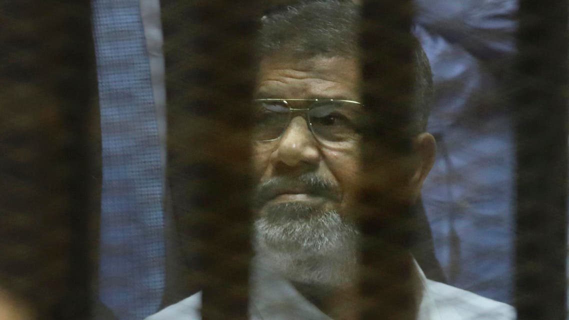 Egypt's ousted Islamist President Mohammed Morsi sits in a soundproof glass cage inside a makeshift courtroom at Egypt's national police academy in Cairo, Egypt, Tuesday, April 21, 2015 (AP)