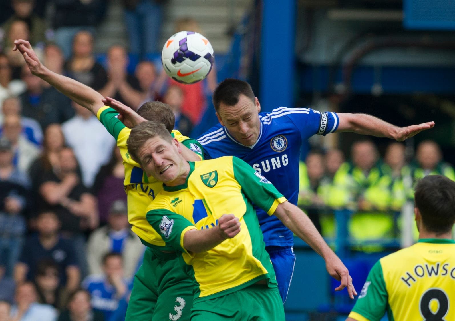 Chelsea's John Terry, right, fights for the ball with Norwich City's Michael Turner, front, and Steven Whittaker, during their English Premier League soccer match, at the Stamford Bridge Stadium in London, Sunday May 4, 2014. (AP Photo/Bogdan Maran)