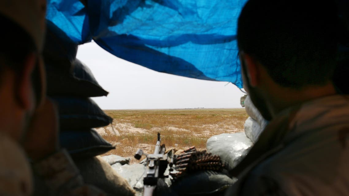 In this Monday, April 20, 2015 photo, two Sunni fighters overlook an ISIS group-held village on the other side of the frontline in northern Iraq. (AP)