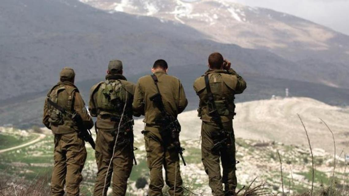 Israeli soldiers deployed on the border look towards Syria. Reuters