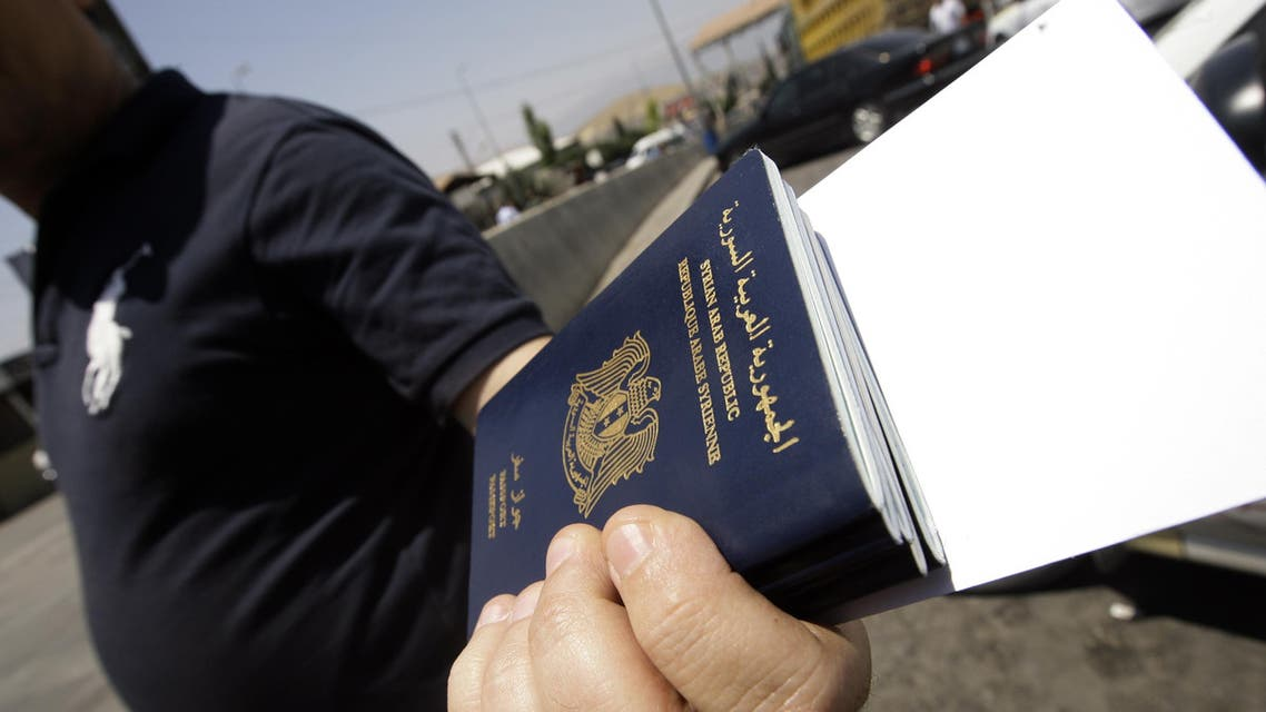 A Syrian man carries passports of relatives before getting them stamped on the Lebanese-Syrian border in al-Masnaa on July 20, 2012. AFP