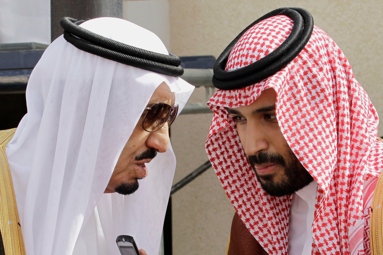 File photo shows King Salman bin Abdul-Aziz Al Saud (L) speaks with his son Prince Mohammed in Riyadh, Saudi Arabia. (AP)
