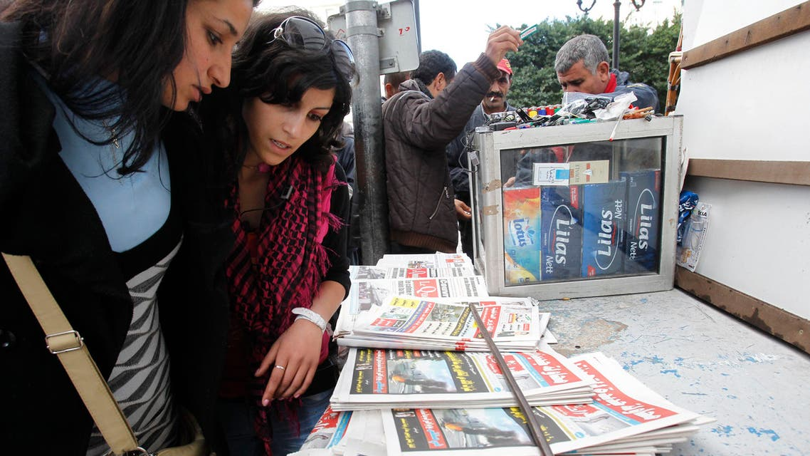 Women check out newspapers in Tunis, Tunisia Thursday, Jan. 13, 2011. AP