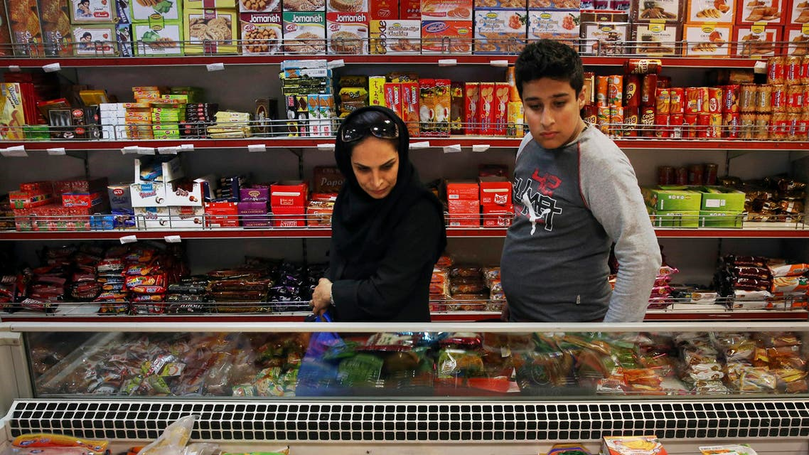 Iranians shop in a supermarket in north Tehran, Iran, Wednesday, April 29, 2015. Iran has scrapped the country's wealthiest citizens off a list of people receiving monthly cash handouts in a small step toward easing the burden on the budget and freeing up more government funds, an official said Wednesday. The move, which will free up about $3 million a month of government money, is the latest in Tehran's efforts to juggle cash and wean the nation off subsidies in an oil-dependent economy suffering from a steep drop in global oil prices. (AP Photo/Vahid Salemi)