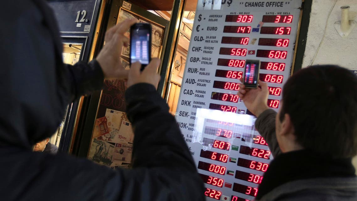 Turks look at currency charts (AP)