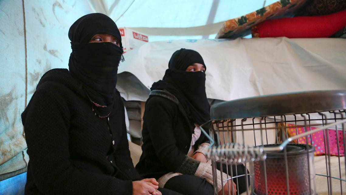 Internally displaced Yazidi women warm themselves by a heater inside their tent at a refugee camp in Bamarny village in Dahuk of the Kurdistan region. (File: AP)
