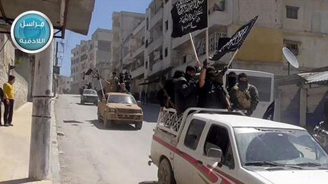 Nusra Front fighters standing on their vehicles and waving their group's flags as they tour the streets of Jisr al-Shughour, Idlib province, Syria. (AP)