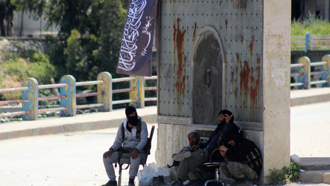 Armed fighters loyal to Al-Qaeda's Syrian affiliate, Al-Nusra Front, sit under a gate at the entrance of the northern town of Jisr al-Shughur on April 26, 2015.  AFP