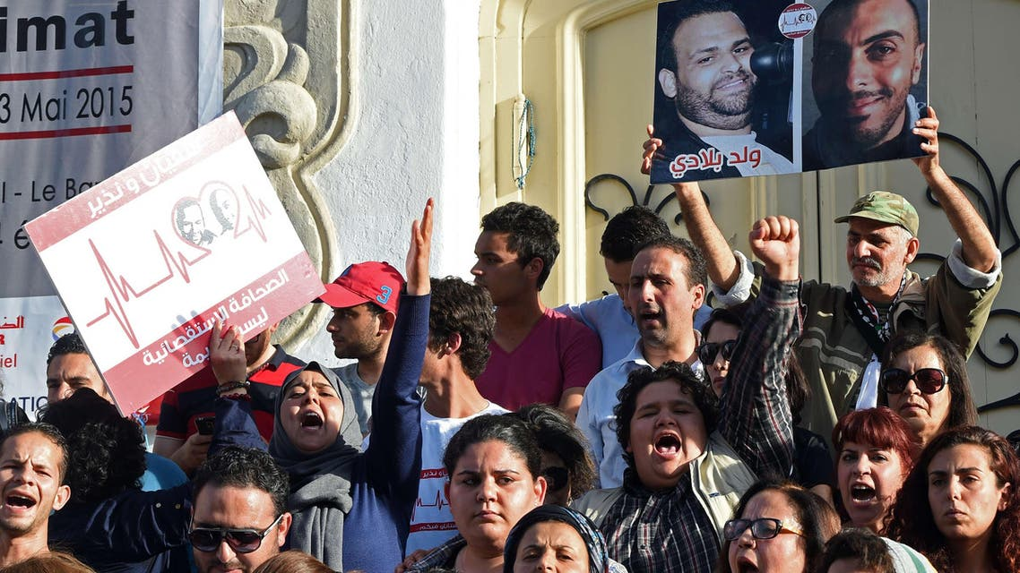 Tunisian journalists shout slogans and hold placards bearing portraits of Sofiene Chourabi and Nadhir Ktari, two of their colleagues who went missing in eastern Libya in September 2014. (AFP)