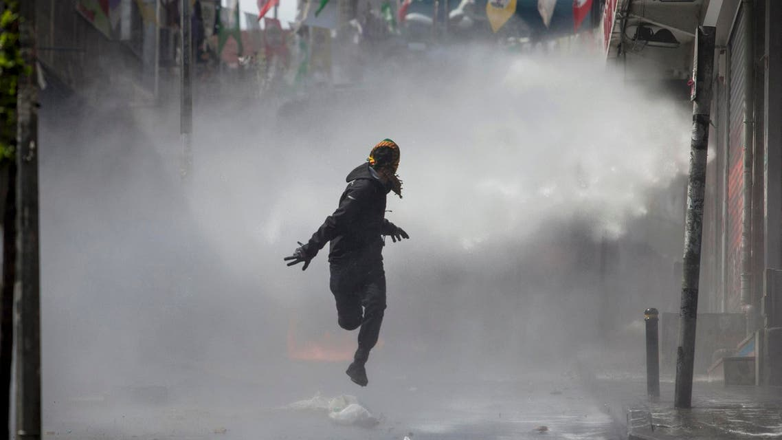 A masked protester runs away from a water cannon's jet during clashes with police in Okmeydani neighbourhood in Istanbul, Turkey, May 1, 2015. (Reuters)