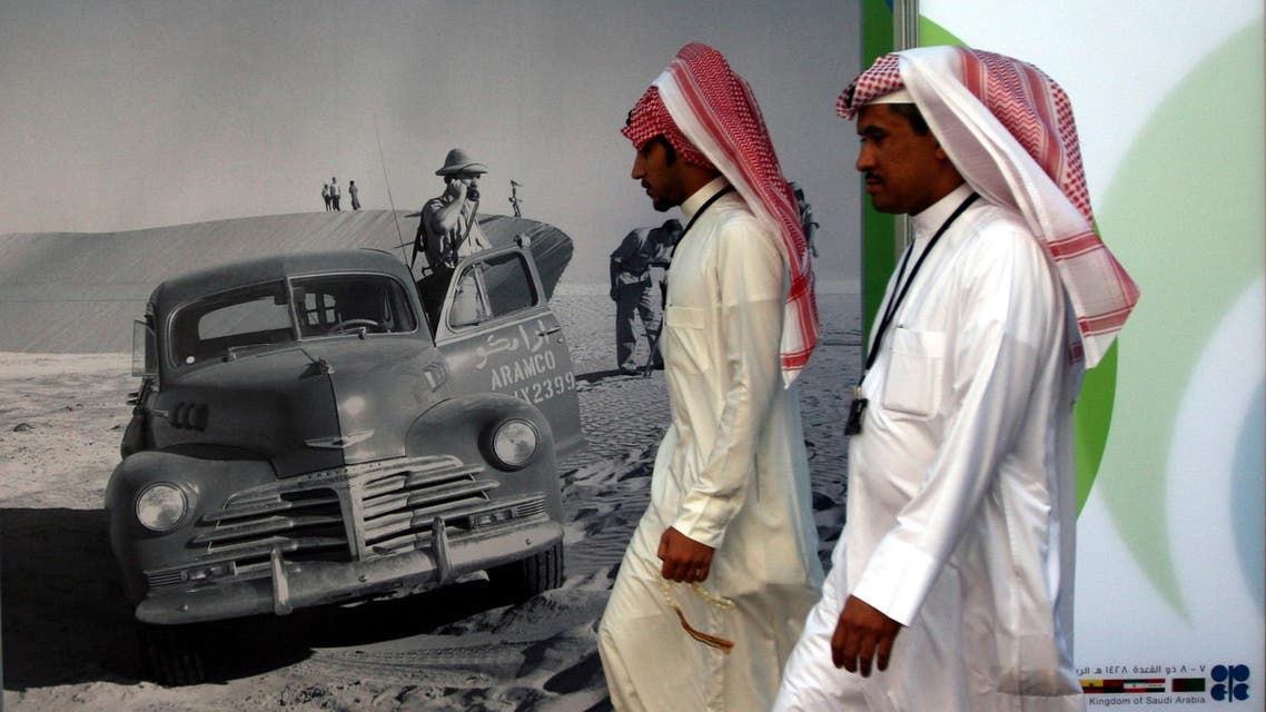 Saudi men walk by an advertisement for U.S. oil company Aramco during the Organization of the Petroleum Exporting Countries (OPEC) Summit in Riyadh, Saudi Arabia. (File: AP)