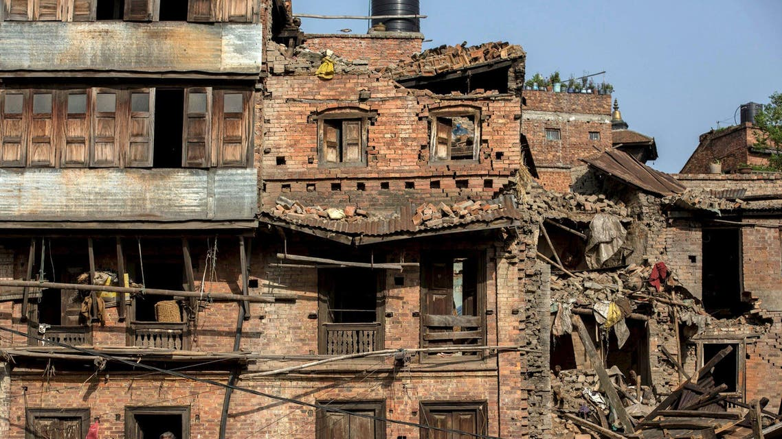 A woman looks out of damaged house following Saturday's earthquake in Bhaktapur. (Reuters)