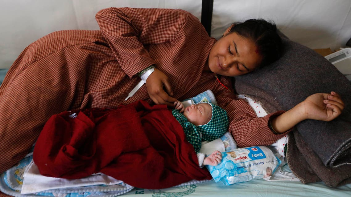 Nepalese woman Lata Chand,19, looks at her newly born baby girl at the Israeli field hospital in Kathmandu, Nepal, Friday, May 1, 2015. (AP)