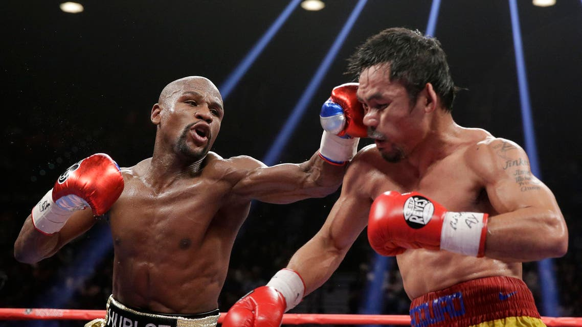 Floyd Mayweather hits Manny Pacquiao during their welterweight title fight on Saturday. (AP Photo/Isaac Brekken)
