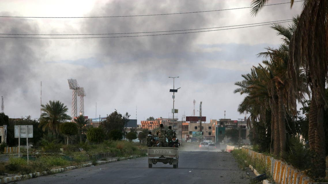 In this photo taken Tuesday, March 31, 2015, Shiite militiamen patrol the streets of Tikrit, Iraq. Iraqi government forces drove the Islamic State group out of Abu Mustafa's hometown of Tikrit over a month ago, but he has yet to return, fearing the Shiite militias that now patrol its bombed and battered streets. (AP Photo/Khalid Mohammed)