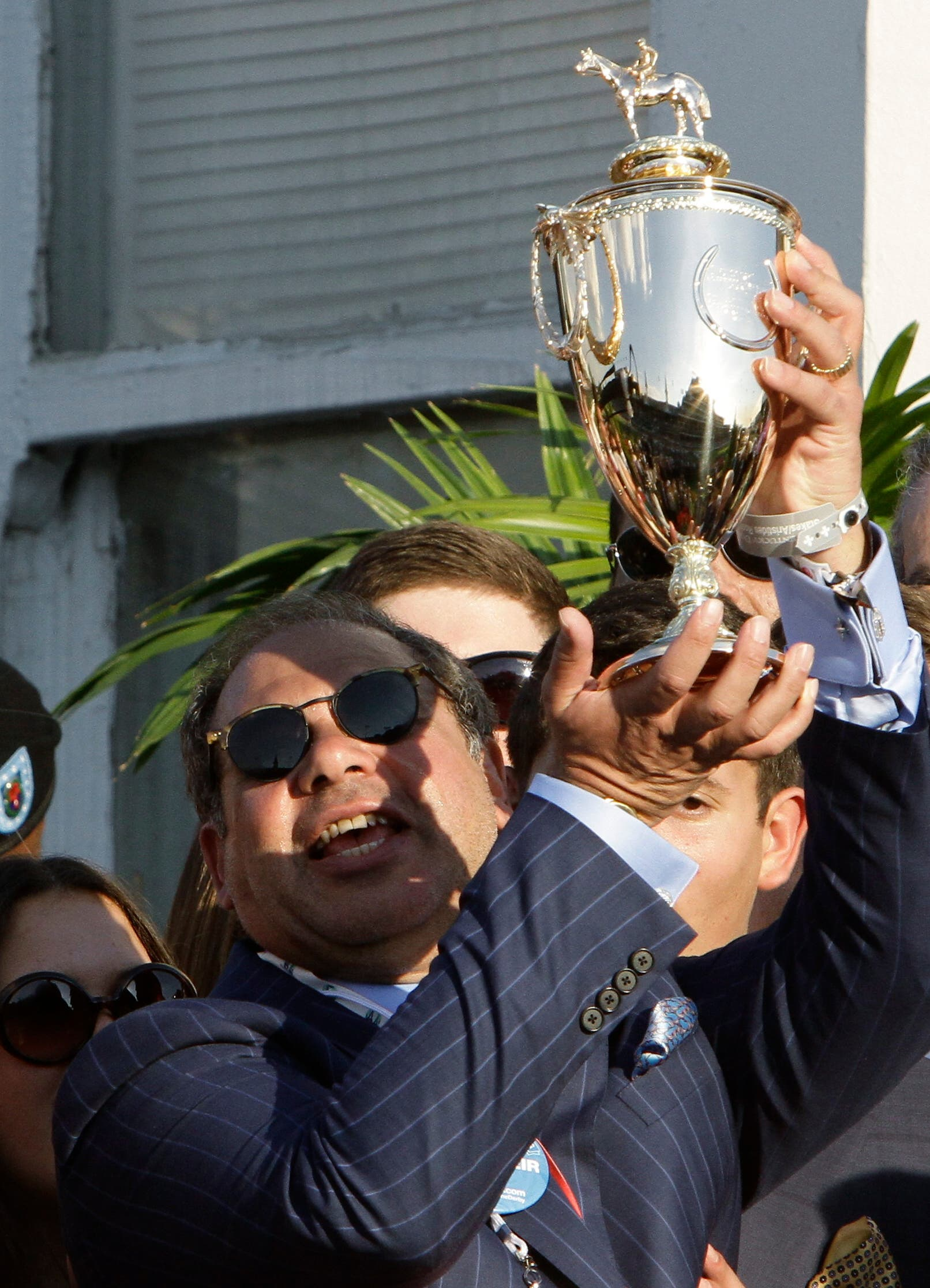 American Pharoah owner Ahmed Zayat holds the trophy after Victor Espinoza rode American Pharoah to victory at the Kentucky Derby horse race at Churchill Downs. (AP)