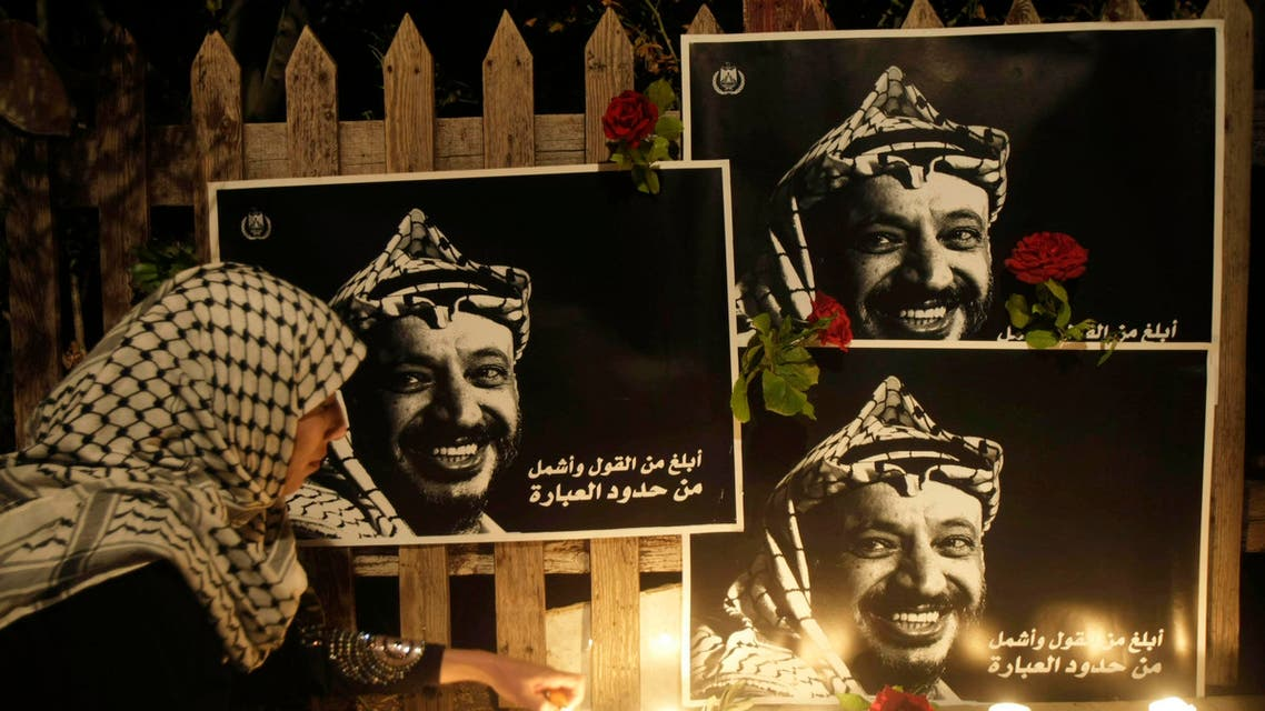 A Palestinian woman lights candles under posters of late Palestinian President Yasser Arafat. (File: AP)