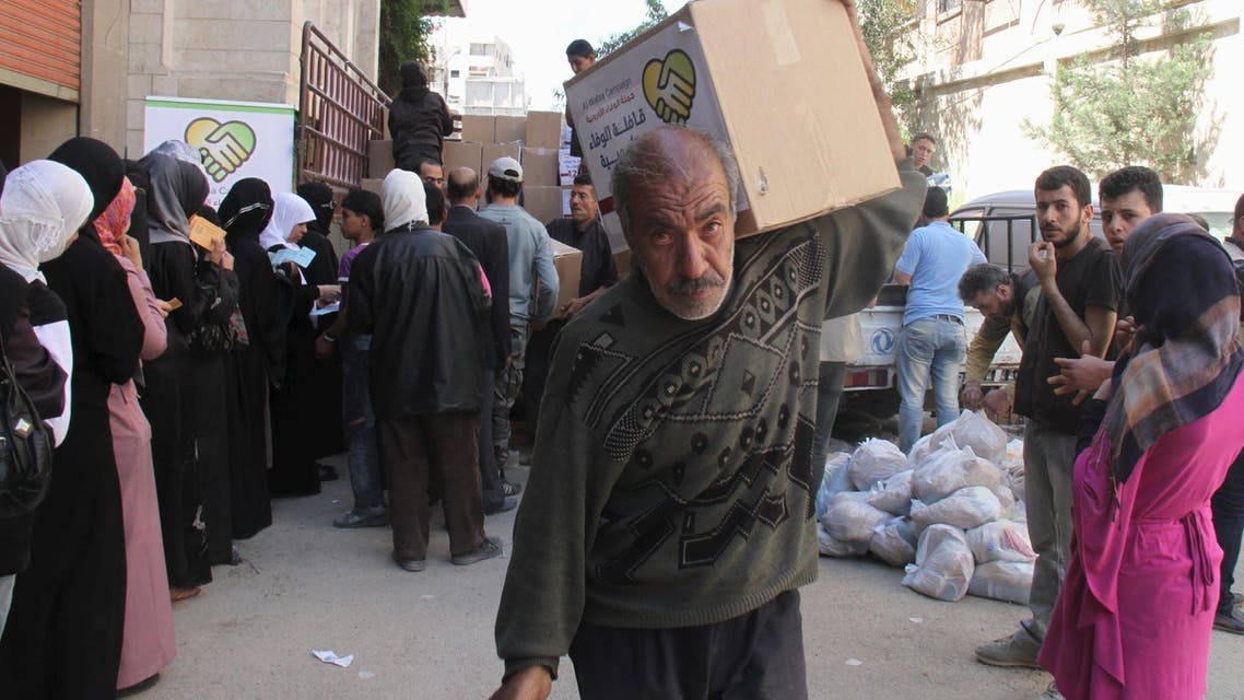 نازح من مخيم اليرموك يتلقى مساعدات إنسانية في منطقة أخرى من دمشق
