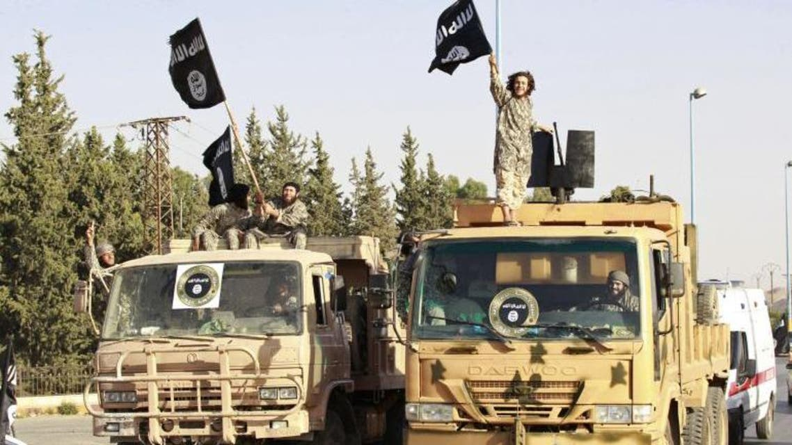 Militant Islamist fighters wave flags as they take part in a military parade in Syria's northern Raqqa province June 30, 2014. Reuters