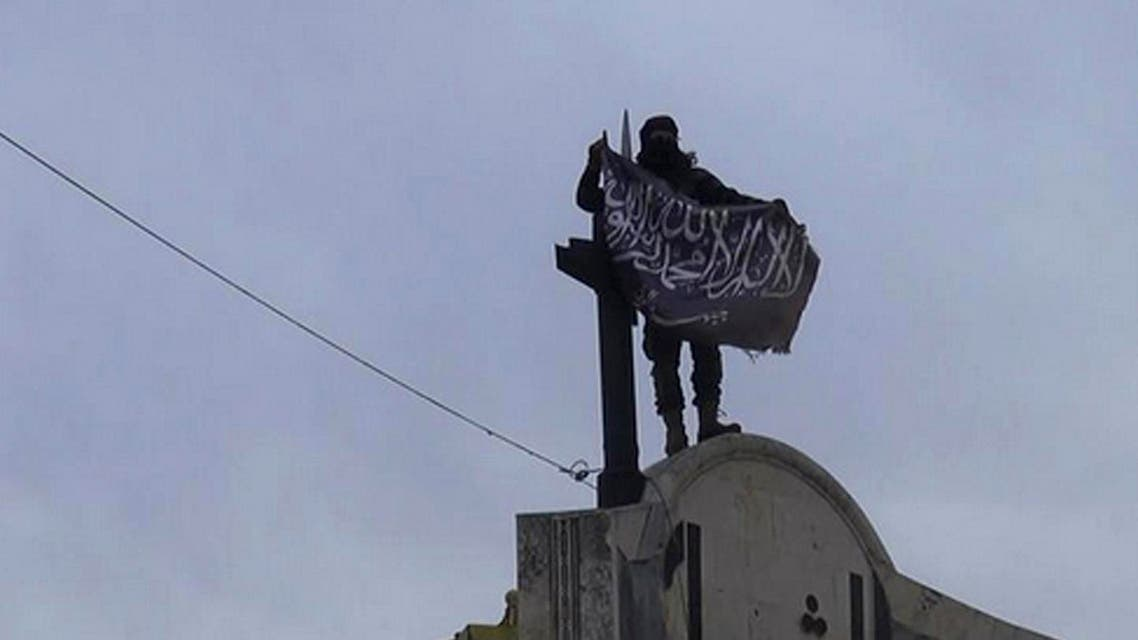 In this file photo posted on the Twitter page of Syria's al-Qaida-linked Nusra Front on Saturday, March 28, 2015, which is consistent with AP reporting, a fighter from Syria's al-Qaida-linked Nusra Front holds his group flag in Idlib province, north Syria. In the span of a month, a coalition of Syrian insurgents has routed government forces across the country's northwest, flushing them out of strongholds in a string of embarrassing loses for President Bashar Assad. (Al-Nusra Front Twitter page via AP, File)