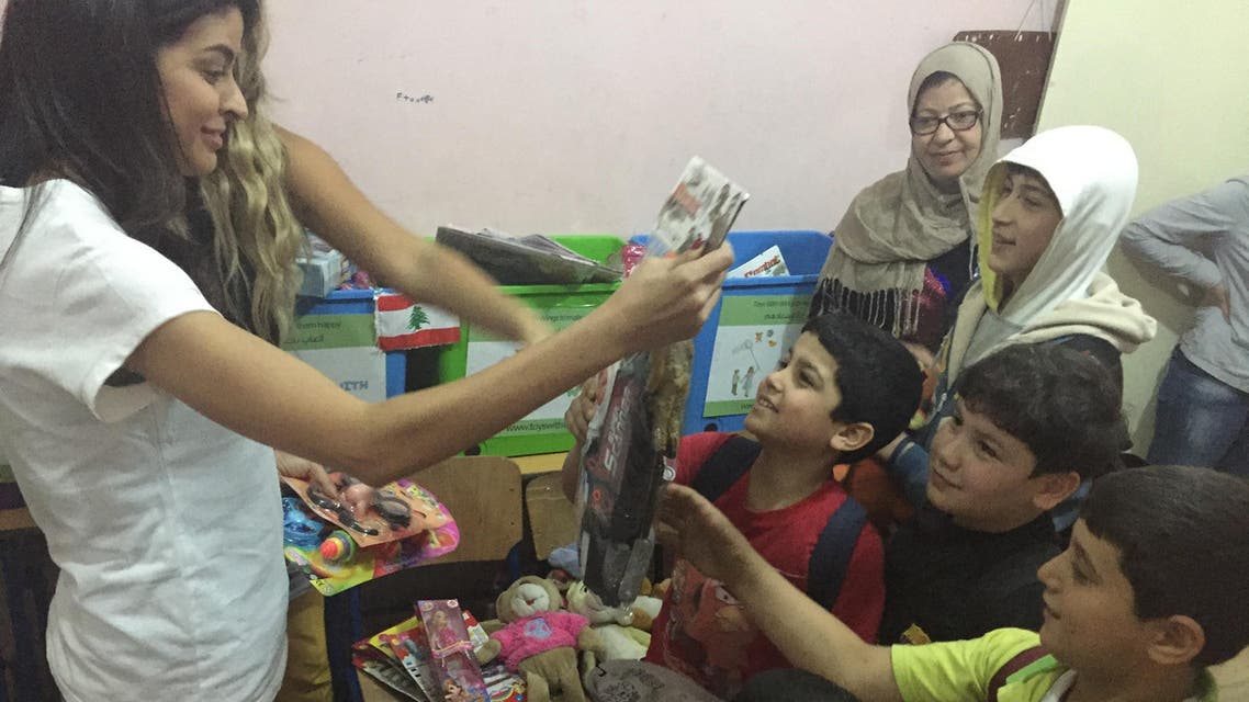 MBC news presenter Mouna Elhaimoud gives out toys at the Shatila refugee camp, Lebanon. (Photo courtesy: Toys With Wings)