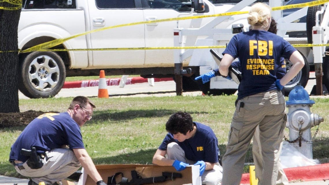 FBI investigators collect evidence, including a rifle, where two gunmen were shot dead after their bodies were removed in Garland, Texas May 4, 2015. (Reuters)