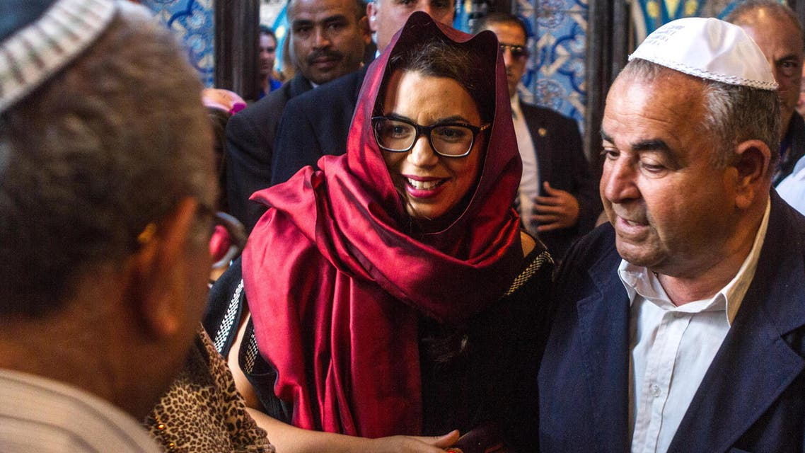 Perez Trabelsi, representative of the Ghriba Jewish community, right, and Tunisian Minister for Tourism Amel Karboul, center, visit the Ghriba synagogue in Djerba, Sunday, May 18, 2014. Despite years of security concerns and a harsh debate over Israeli passports, officials said Sunday the number of Jewish pilgrims taking part in an annual rite in Tunisia is up dramatically for the first time in years. (AP Photo/Aimen Zine)
