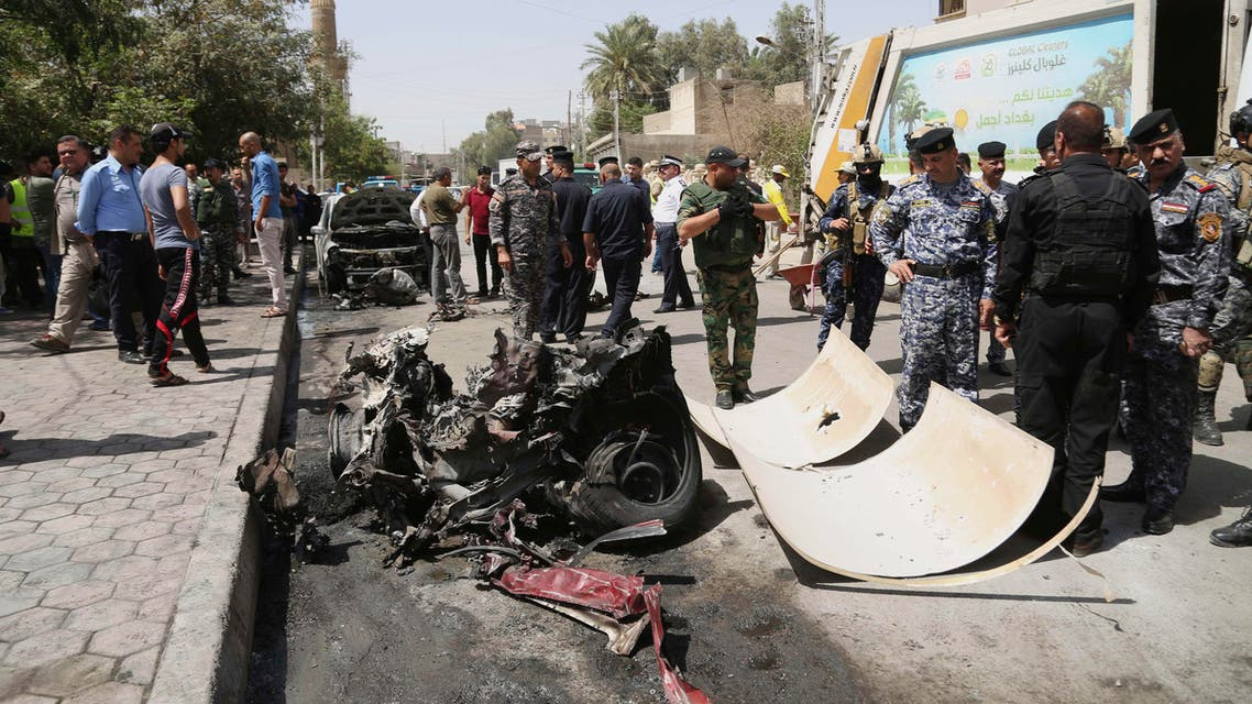 Civilians and security forces gather at the scene of a car bomb explosion near Khudairi mosque in Karrada neighborhood, Baghdad, Iraq, Tuesday, May 5, 2015. A car bomb exploded in the central Karrada commercial area killing several people, according to police and medical officials. The area where the car exploded included restaurants, shops and a Sunni mosque. (AP Photo/Khalid Mohammed)
