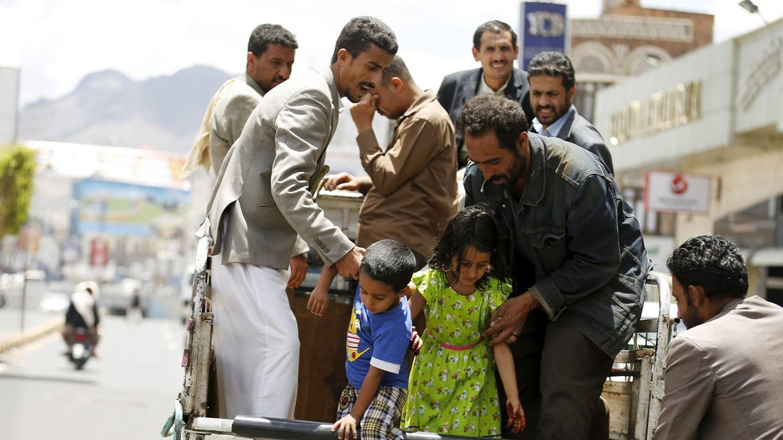 People help children step out of a truck taxi in Yemen's capital Sanaa May 6, 2015. REUTERS