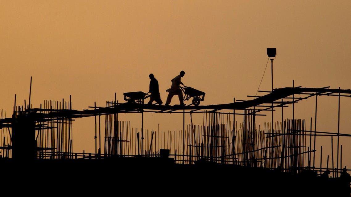 Pakistani laborers are silhouetted against the skyline as they work on the top of a construction site in Islamabad, Pakistan, Wednesday, March 14, 2012. (AP Photo/Anjum Naveed)