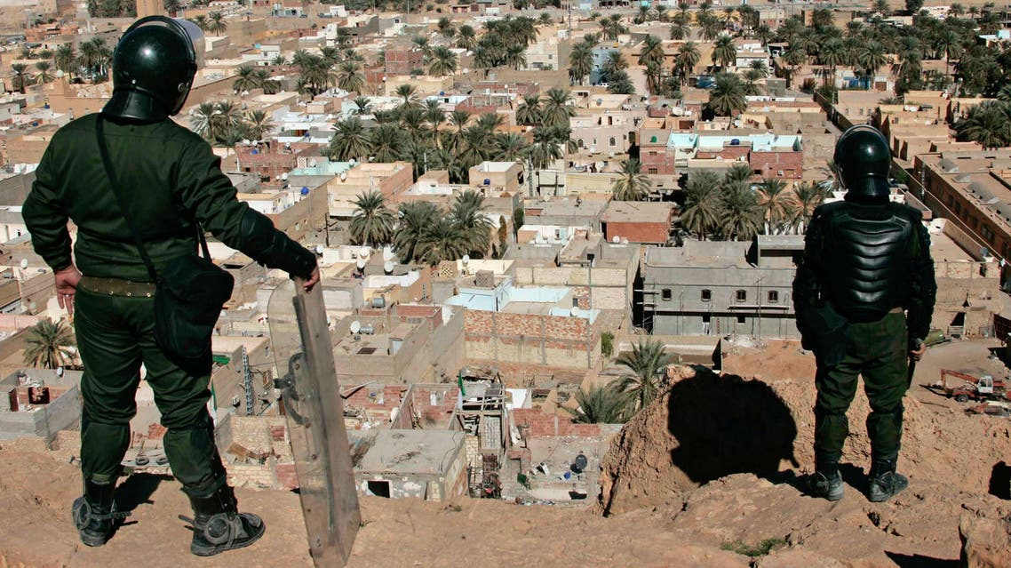 Algerian police officers watch over the desert city of Ghardaia, southern Algeria, after a Berber died of his wounds on Thursday, Ghardaia, Saturday, Feb. 8, 2014.