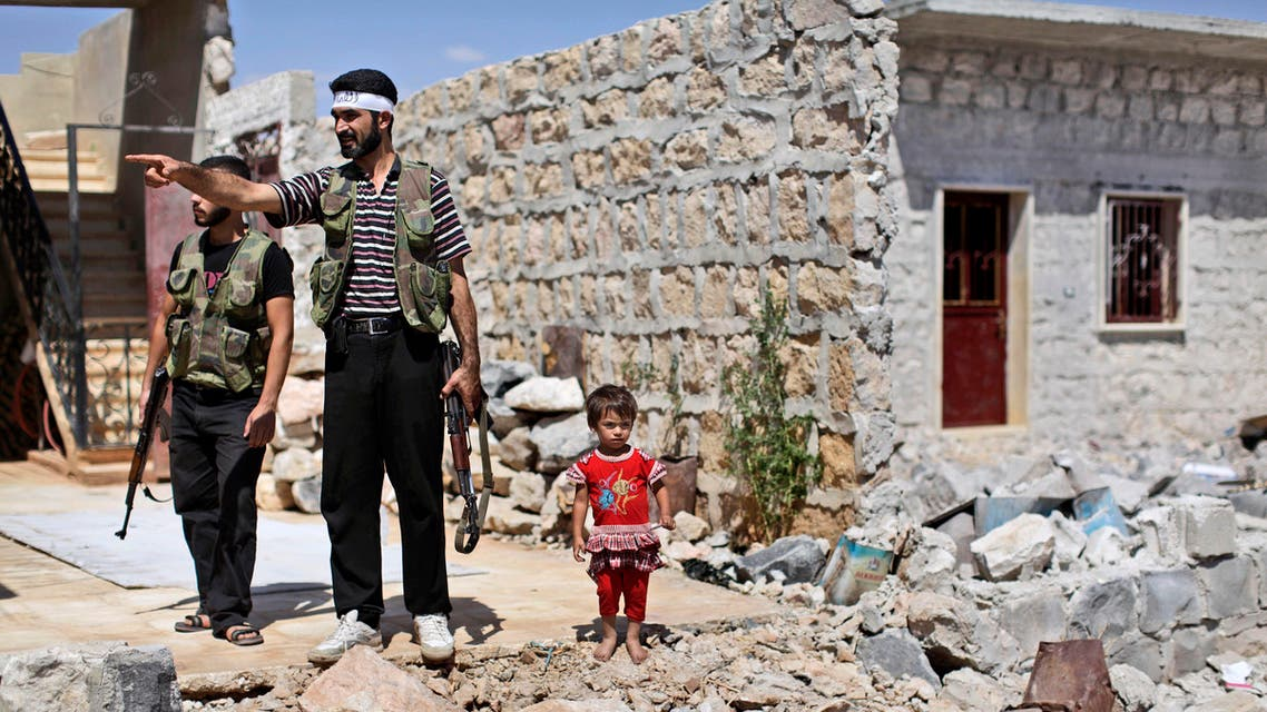 A Syrian child stands next to rebel fighters checking a house that was damaged in bombing by government forces in Marea, on the outskirts of Aleppo, Syria, Tuesday, Sept. 4, 2012. (Associated Press)
