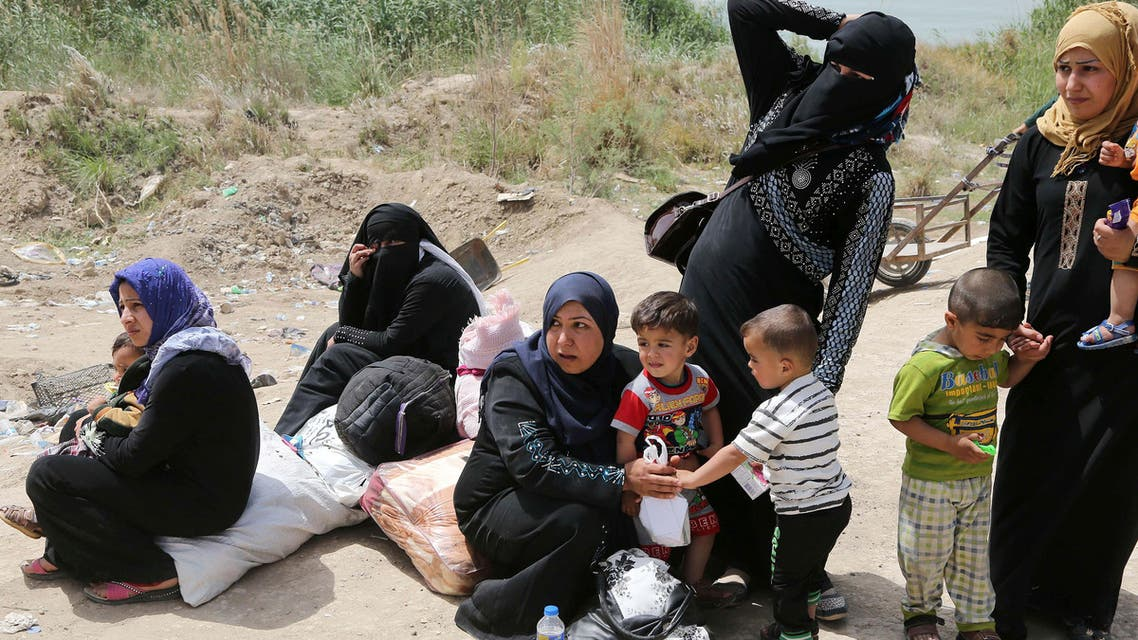 Women hold their children as displaced people from Ramadi cross Bzabz bridge 65 km west of Baghdad, Iraq, Saturday, April 18, 2015. Thousands of displaced people form Ramadi city continue to pour to Baghdad, fleeing the ongoing fighting in Anbar provincial capital between Iraqi security forces and fighters from Islamic State militant group. (AP Photo/Karim Kadim)