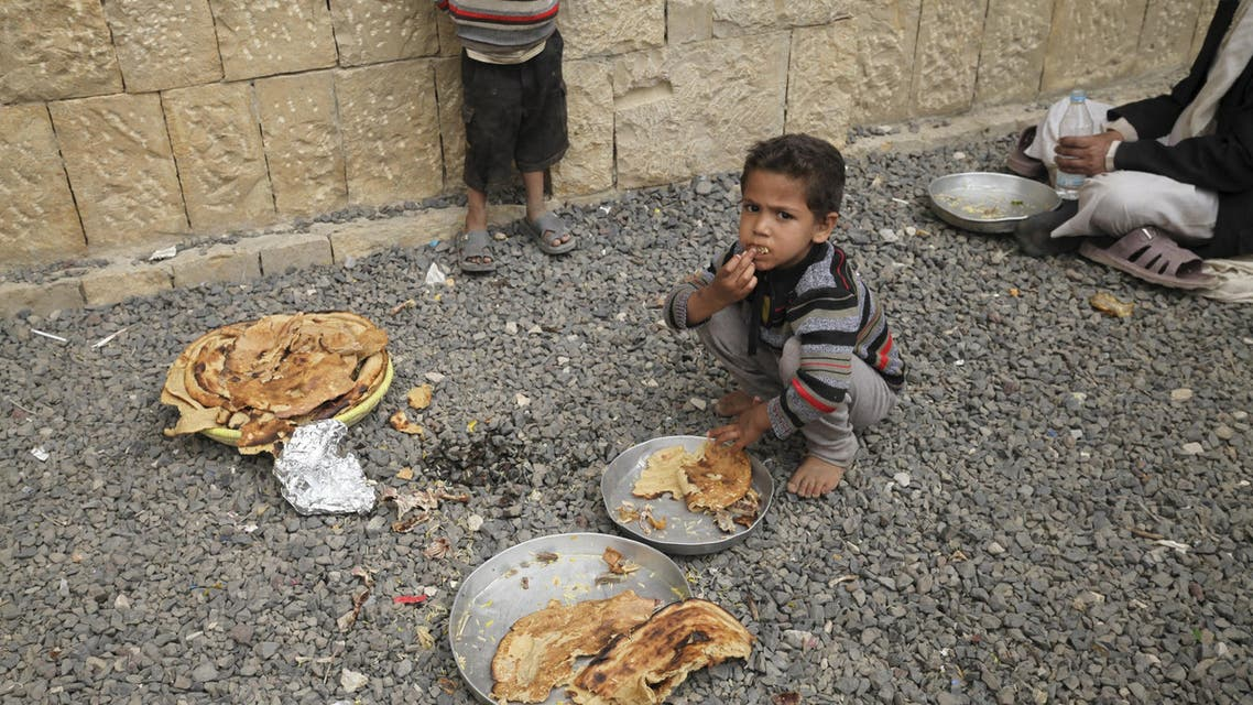 A boy eats with other internally displaced people in a school in the district of Khamir of Yemen's northwestern province of Amran