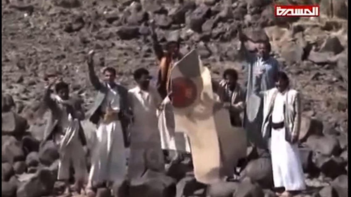 An image grab taken from the Huthi rebel television station Al-Masira shows Yemeni tribesmen celebrating around the wreckage of a plane bearing a Moroccan flag, in the the Wadi Nushur area in the north Yemen's province of Saada, on May 11, 2015. Yemeni rebels said they shot down a fighter jet as Saudi-led coalition air strikes intensified a day ahead of a hoped-for five-day humanitarian truce. Morocco announced that one of its warplanes taking part in operations against the rebels was missing along with its pilot, and that a search was underway.