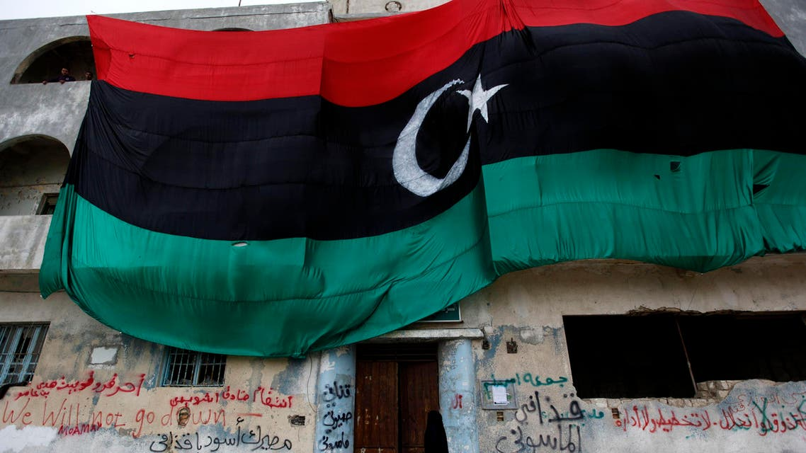 A Libyan woman steps inside a building which is dressed with a huge old Libyan flag, in Benghazi, eastern Libya, on Friday March 4, 2011. (AP)