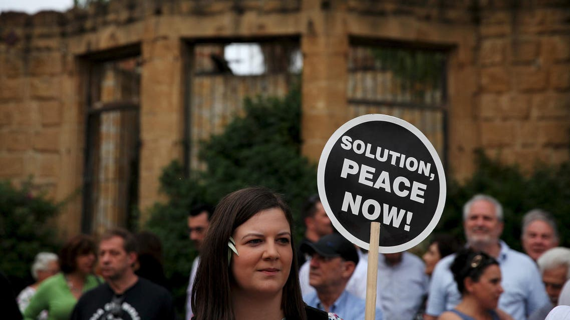 A woman holds a placard during a demonstration in favour of a peace settlement on divided Cyprus, outside a venue where leaders of estranged Greek and Turkish Cypriots met, in Nicosia, May 11, 2015. It was the first encounter of Greek Cypriot leader Nicos Anastasiades and Turkish Cypriot leader Mustafa Akinci since Akinci, a leftist moderate, won leadership elections in northern Cyprus on April 26. REUTERS/ Yiannis Kourtoglou