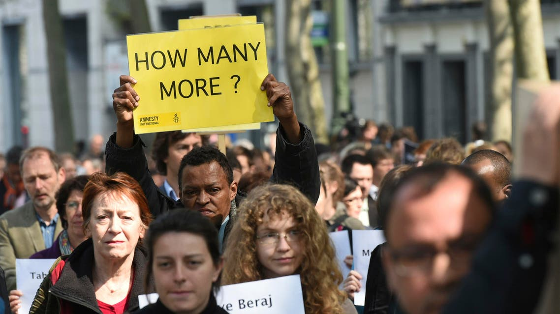 A protestor holds up a sign as others carry a mock coffin of a migrant during a demonstration outside of an emergency EU summit in Brussels on Thursday, April 23, 2015. (File Photo: AP)