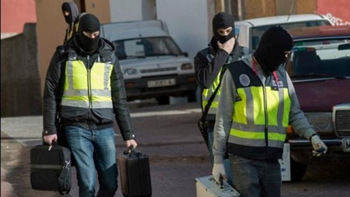 Masked Spanish police officers carry cases from an apartment during an operation in Melilla, December 16, 2014. (File Photo: Reuters)
