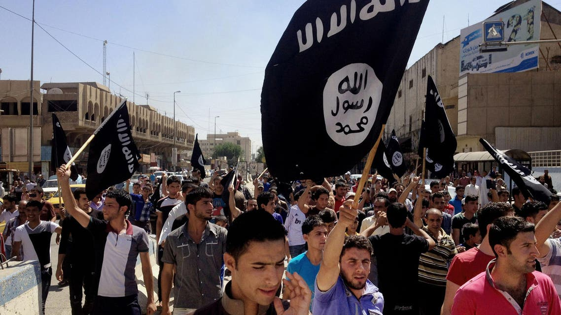 "In this Monday, June 16, 2014 file photo, demonstrators chant pro-Islamic State group slogans as they wave the group's flags in front of the provincial government headquarters in Mosul, 225 miles (360 kilometers) northwest of Baghdad, Iraq. The IS declaration of a ""caliphate"" in Iraq and Syria inspired a stream of thousands of foreign fighters to join it and earned it pledges of allegiance by individual militants around the region. (AP Photo, File)"
