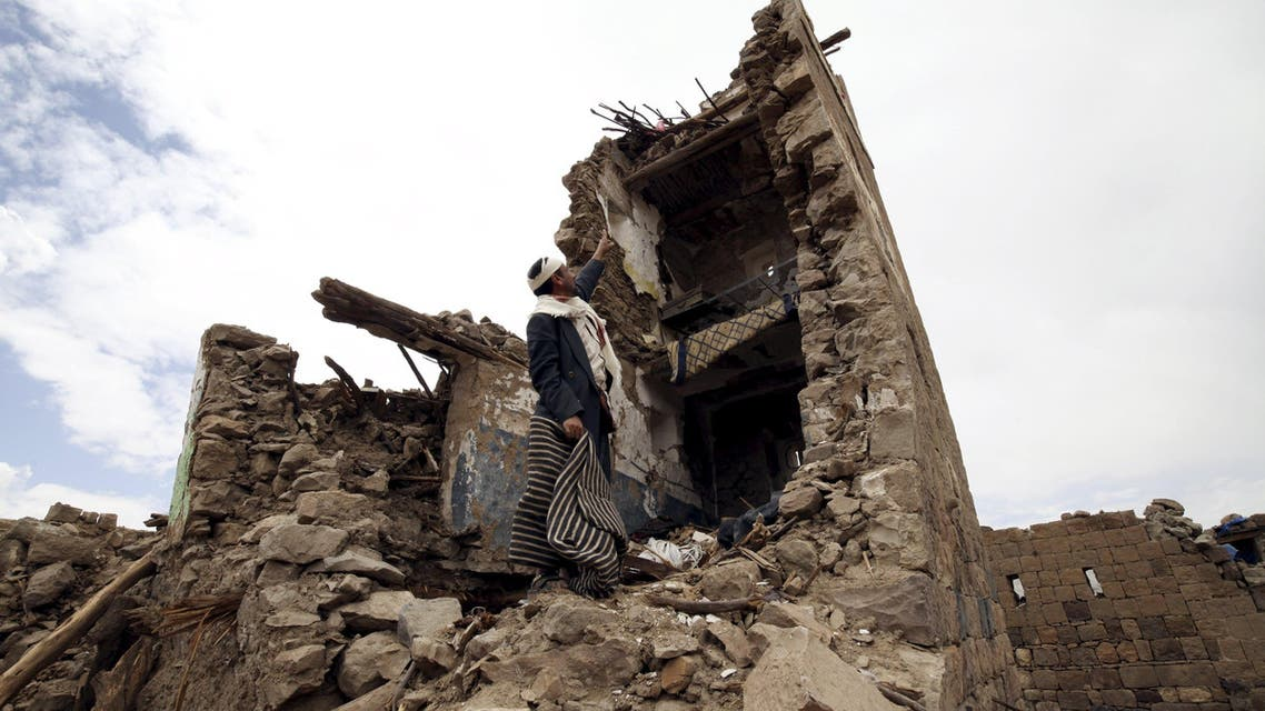 Man points up at a house that was damaged during an airstrike carried out by the Saudi-led coalition in Faj Attan village, Sanaa, Yemen. (Reuters)