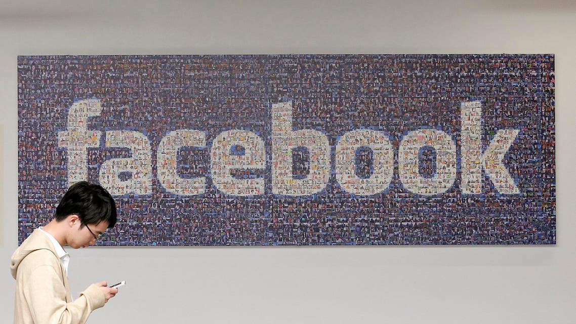 In this Wednesday, June 11, 2014 photo, a man walks past a sign in an office on the Facebook campus in Menlo Park, Calif. One more time, Facebook is trying to simplify its lengthy privacy policy — and make it much shorter — to explain how it targets advertisements to its 1.35 billion users. (AP Photo/Jeff Chiu)