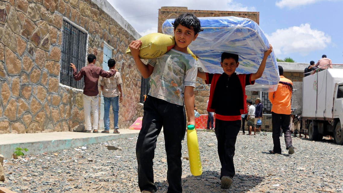 Boys carry relief supplies to their families who fled fighting in the southern city of Aden, during a food distribution effort by Yemeni volunteers, in Taiz, Yemen, Saturday, May 9, 2015.