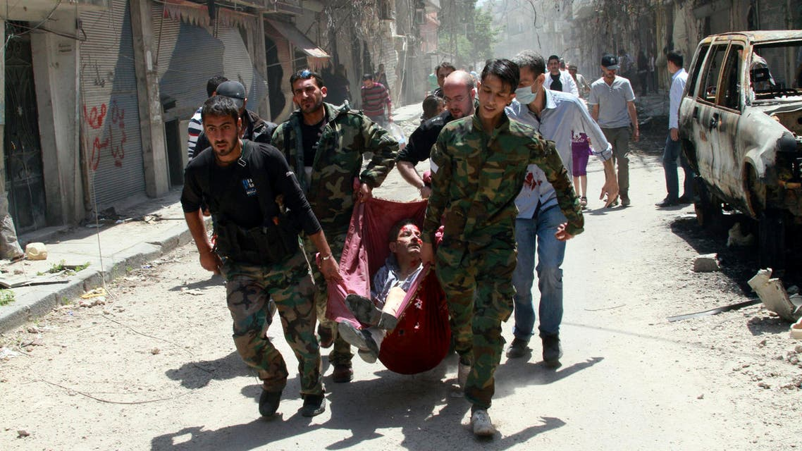 Rescuers carry a man wounded by a mine that went off in Homs, Syria. AP