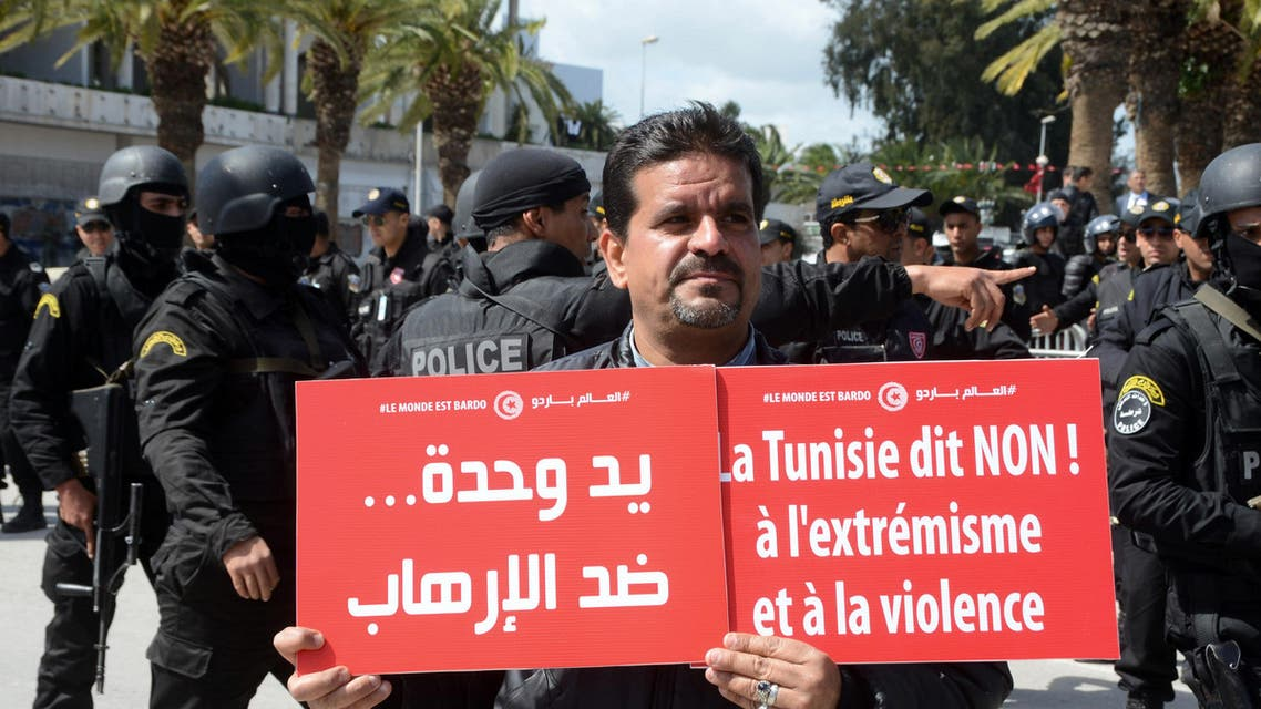 """A protestor holds placards reading """"Tunisia says no to extremism and violence"""" during an anti-extremism march, in Tunis, Sunday, March 29, 2015. Tens of thousands of Tunisians from across the political spectrum marched through the capital Sunday to denounce extremist violence after a deadly museum attack on foreign tourists. Hours ahead of the rally, security forces killed nine terrorist suspects in raids around the country. (AP Photo/Hichem Jouini)"""