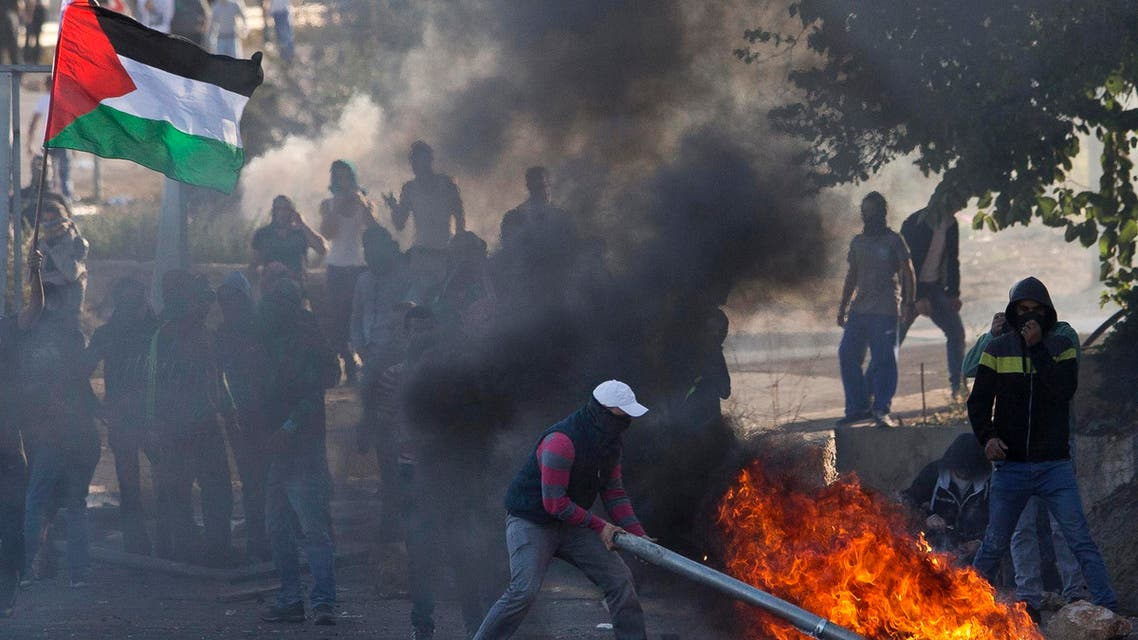In this Nov. 9, 2014 file photo Israeli Arab protestors, one burning a traffic sign as another waves a Palestinians flag, clash with Israeli riot police in the Arab village of Kfar Kana, northern Israel. AP